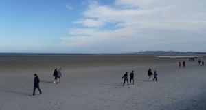 People walk along Sandymount strand in Dublin practising social distancing on March 20th. Photograph: Clodagh Kilcoyne/File Photo