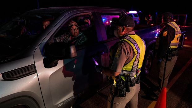 Navajo police officers inform drivers near about the nightly curfew caused by coronavirus. The 200-strong force is charged with enforcing the 8pm curfew every night. Photograph: Adriana Zehbrauskas/New York Times