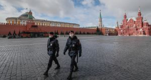 Police officers wearing protective masks walk on the Red Square in front of the Kremlin in Moscow on Friday.  Photograph: Yuri Kochetkov/EPA