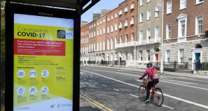 A cyclist passes by a bus stop with a public health warning on Covid-19 in Dublin. Over the last few weeks we've seen what can be achieved when the State mobilises financial, organisational and human resources for the common good.Photograph: Aidan Crawley/EPA