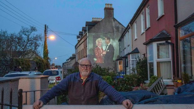 Con Sheehan, self-isolating of Windmill Road, Cork, enjoys a wall projection film shown by Scott Duggan for his neighbours. Photograph: Clare Keogh