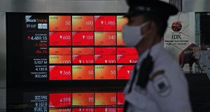 A member of security wearing a protective mask stands in front of an electronic board displaying stock prices at the lobby of the Indonesia Stock Exchange  in Jakarta, Indonesia. Photograph: Dimas Ardian/Bloomberg