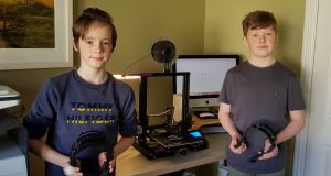 Daire and ConorJean with their 3D printer which is generating face masks for healthcare workers.