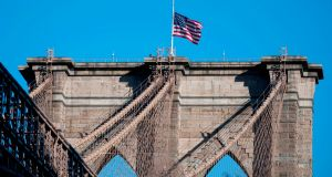 The US flag is seen at half-mast on the Brooklyn Bridge in New York on April 11th. Photograph: Johannes Eisele/AFP via Getty Images