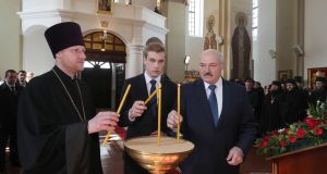 Belarusian President Alexander Lukashenko (R) and his son Nikolai (middle) light candles at an Orthodox Easter service. Photograph: Nikolai Petrov/EPA