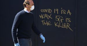 A man walking past graffiti in London. There has been a spate of attacks on the 5G network linked to erroneous claims that it is responsible for the spread of coronavirus.  Photograph: EPA/Neill Hall