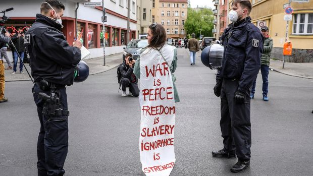 Riot police escort a demonstrator wrapped in a banner that reads War Is Peace, Freedom Is Slavery, Ignorance Is Strength – a quote from George Orwell's novel 1984. Photograph: EPA
