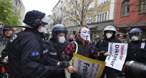 Police remove a demonstrator during a protest against coronavirus  restrictions in Berlin. Photograph: Getty
