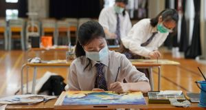A  student wearing a mask takes part in a final secondary school exam in Hong Kong. Photograph: Kin Cheung/AP