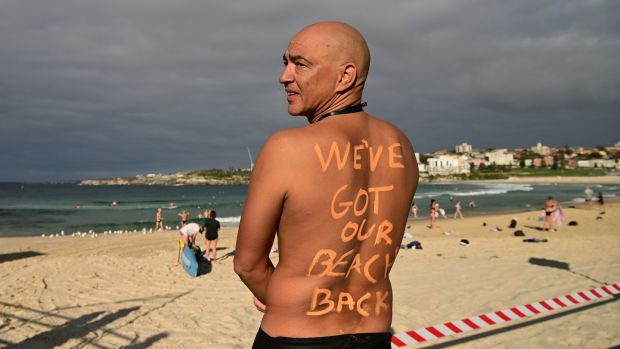 A man poses for a photo at Bondi Beach following its reopening to the public in Sydney, Australia, on Tuesday. Photograph: Joel Carett/EPA