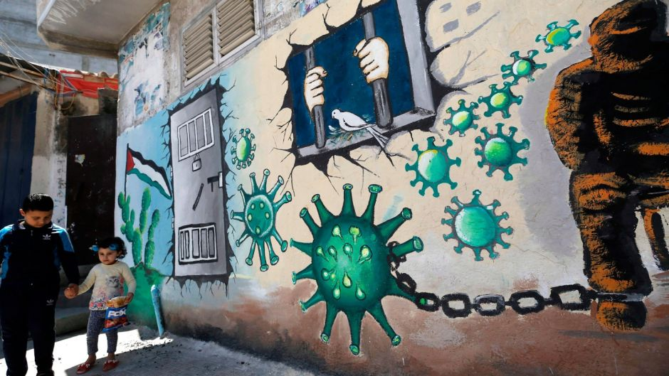 Palestinian children walk past a mural depicting the coronavirus and a prison cell, in Gaza City during the coronavirus pandemic on April 28th. Photograph: Mohammed Abed/AFP via Getty