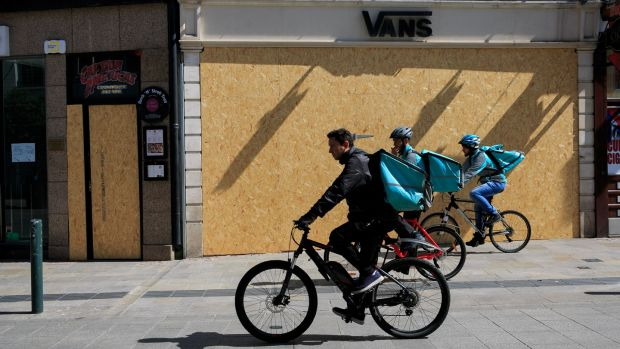 14/04/2020Deliveroo cyclists pass by Boarded up restaurant Captain Americas & Vans store on Grafton Street Dublin.Photo:Gareth Chaney/Collins