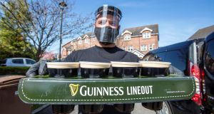 Harry McKeaveney from The Hatfield House bar, Belfast, wearing PPE as he delivers pints of Guinness. Photograph: Paul Faith/Getty/AFP
