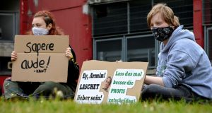 Students wearing protective face masks show banners reading 'Better let the professionals decide!', as they protest against the opening of schools, in Dusseldorf, Germany. Photograph: EPA/Sascha Steinbach