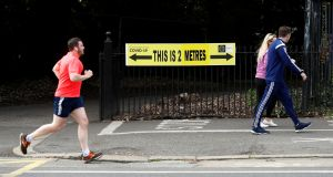 People are seen jogging past a social distancing sign in the Phoenix Park in Dublin last week. Photograph: Jason Cairnduff/Reuters
