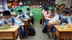 Students wear plastic face shields at the Nankan Junior High School in Taoyuan City, Taiwan: testing, contact tracing, travel bans, quarantines and masks in public places are Asian defence tools. Photograph: David Chang