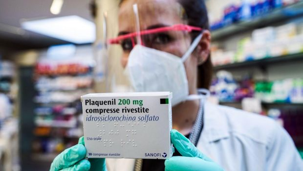 A pharmacist in Turin with a pack of Pasquenil, the new drug based on hydroxychloroquine. Photograph: Tuno Romano/EPA