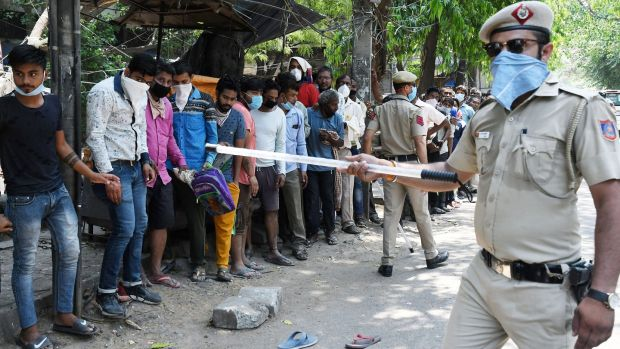 Indian police officers try to enforce social distancing as people queue for a liquor shop in New Delhi. Photograph: EPA/STR