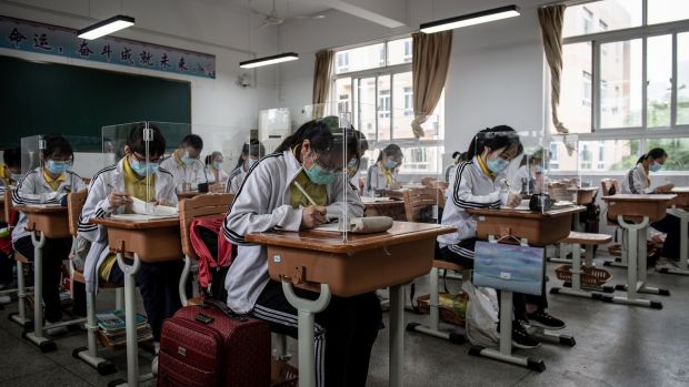 High school students study with plastic partitions in a classroom in Wuhan, with 121 schools reopening in province on Wednesday. Photograph: STR/AFP/Gtty