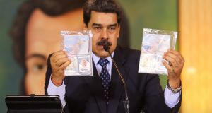 Venezuelan president Nicolas Maduro showing the passports of two US citizens arrested by security forces in his country after an alleged failed plot to capture him. Photograph: Marcelo Garcia/Venezuelan Presidency/AFP via Getty Images.