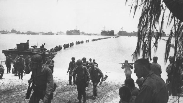 Army reinforcements disembarking from LSTs form a graceful curve as they proceed across coral reef toward the beach at Saipan in summer 1944 Saipan.