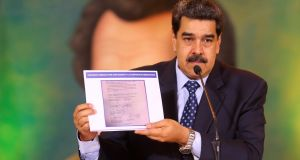 Venezuelan president Nicolás Maduro holds a copy of a document he says is evidence of     opposition leader Juan Guaidó's involvement in a plot to oust him, at a press conference in Caracas on  Wednesday. Photograph: Miraflores Palace presidential press office via AP