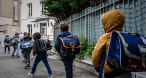 Pupils proceed to their classroom  at a private Catholic school in Paris. Some children returned to school in France on Tuesday. Photograph: Philippe Lopez/Getty/AFP