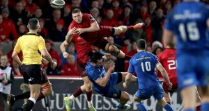 Munster's Andrew Conway contests a high ball with Leinster's James Lowe during the Guinness Pro 14 game at  Thomond Park in December 2018. Photograph: Dan Sheridan/Inpho