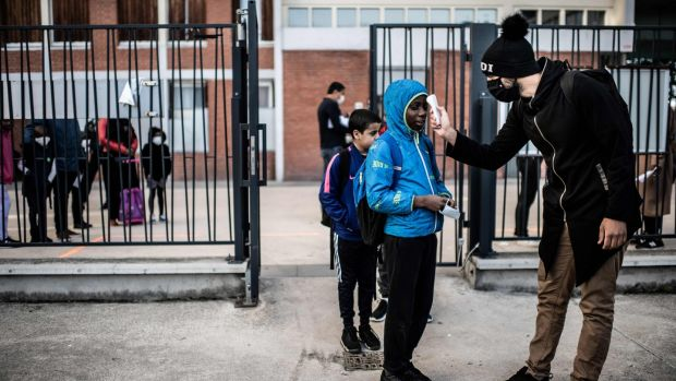 Pupils have their temperature checked before entering the entering the Saint-Exupery school in the Paris' suburb of La Courneuve on May 14th as primary schools in France re-open this week after an almost two-month closure. Photograph: Martin Bureau/AFP via Getty