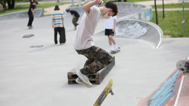 A skateboarder wearing a facemask uses a reopened skatepark in Warsaw, Poland. Photograph: Leszek Szymanski/EPA