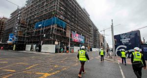 Construction workers make their way to a site along the quays in Dublin. Photograph: Paul Faith/AFP via Getty