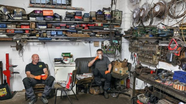 Mechanics Dave Madden and Shane Farrell take a break from work in Farrells Garage which opened again on Monday. Photograph: Joe O'Shaughnessy.