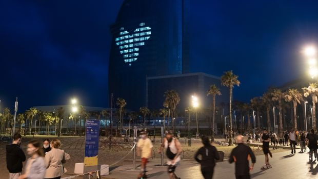 People exercise along the beachfront near the W Hotel, with a giant heart glowing on its facade, in Barcelona, Spain. Photograph: Samuel Aranda/The New York Times