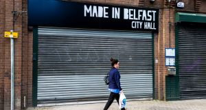 A woman walks past shuttered businesses in Belfast. Photograph: Liam McBurney/PA Wire