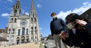 Two worshippers, Guillaume and Cynthia,  put on their as they prepare to enter the reopened Notre Dame de Chartres cathedral in central France on May 14th. Photograph: Jean-François Monier/AFP via Getty Images
