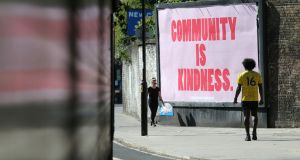People walk past a billboard near Arsena's Emirates Stadium. Photograph: Isabel Infantes/Getty/AFP