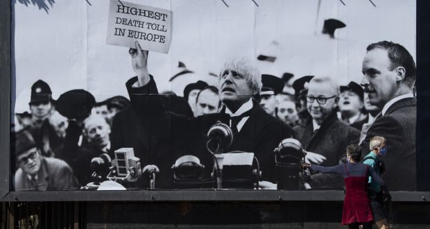 "A woman points towards a satirical poster from the group Led By Donkeys depicting Boris Johnson as former British prime minister Neville Chamberlain delivering his ""Peace for Our Time"" speech, Kentish Town, London,  on May 19th. Photograph: Justin Setterfield/Getty Images"