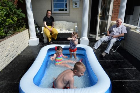 COOL IN THE POOL: Brax Byrne, Isobella Byrne and India Gifford enjoy playing in a paddling pool, while watched by Leon Preston and granddad Philip Preston in Seville Place, Dublin. Photograph: Dara Mac Dónaill/The Irish Times
