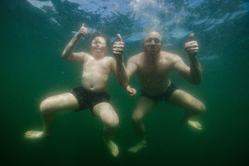 BACK IN THE DEEP: Derek Halpin with his son, Ewan, plunging into the Irish Sea at the Forty Foot. The popular bathing spot in south Dublin has reopened to the public. Photograph: Bryan Keane/Inpho
