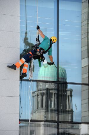 HIGH CLEANING: Martin Gunda cleans windows while abseiling down the 1GQ building on George's Quay, Dublin. Photograph: Dara Mac Dónaill/The Irish Times