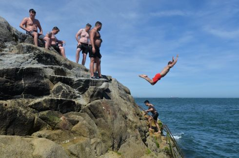 CLIFF DIVING: Visitors to the Forty Foot jump from the rocks into the Irish Sea. The popular Dublin swimming area is open to the public again as Covid-19 restrictions are eased across the Republic. Photograph: Alan Betson/The Irish Times
