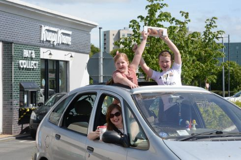 DRIVE-THROUGH DONUTS: Marcella Hunt, a nurse at the Bon Secours Hospital in Glasnevin, with her children, Gemma (8) and Adam (10), after getting free donuts and coffee at Krispy Kreme in Blanchardstown, Dublin.