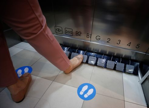 UNDER CONTROL: A shopper pushes the pedals of a foot-operated elevator at Seacon Square shopping mall in Bangkok, Thailand. The special controls were installed in lifts as part of measures to curb the spread of coronavirus.  Photograph: Narong Sangnak/EPA