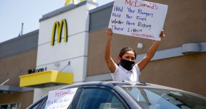 A protester waves a sign from a car during a nationwide strike in the US by McDonald's workers who claim the company has not done enough to protect them during the coronavirus crisis. Photograph: EUGENE GARCIA/EPA