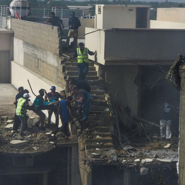 Rescue workers evacuate the site after a Pakistan International Airlines aircraft crashed in a residential neighbourhood in Karachi. Photograph: Asif Hassan/AFP/Getty Images