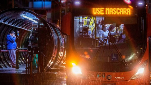 "Commuters wearing face masks travel on a public bus with an electronic sign reading ""Wear a face mask"", in Curitiba, Brazil on Friday. Photograph: Getty Images"