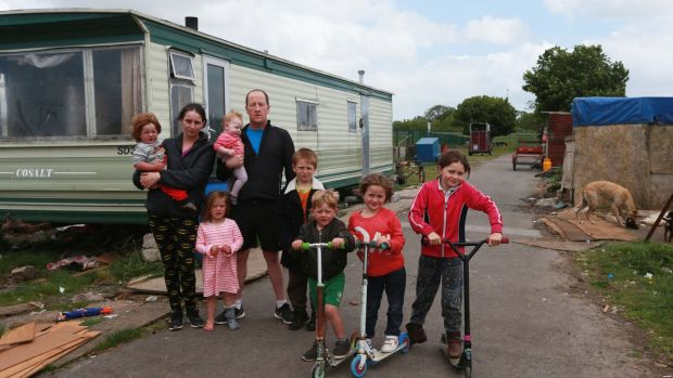 Bridget Harty and Johnny Reilly with seven of their nine children, Mikey (18 months), Judy (3), Nelly (6 months), Danny (7), Joe (4), Diane (6) and Biddy (8) beside one of two trailers the family live in on a halting site just off the M8 at Cashel, Co Tipperary. Photograph: Laura Hutton