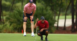 Tiger Woods reads a putt on the sixth green as playing partner Peyton Manning looks on. Photograph: Mike Ehrmann/Getty
