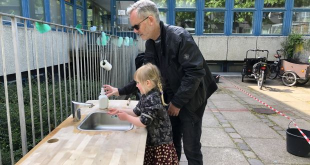 Brendan Sweeney and daughter Theresa (4) outside her daycare centre in Copenhagen. 'Before you even go into the building, they have set up portable wash-hand basins with running water and soap and paper towels,' says Brendan, who is originally from Co Cavan.