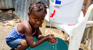 Cherica, two-and-a-half-years-old, washes her hands in front of her grandmother's home in Cite Soleil slum, a district of Port-au-Prince, Haiti.  Photo: Dieu Nalio Chery/ Concern Worldwide